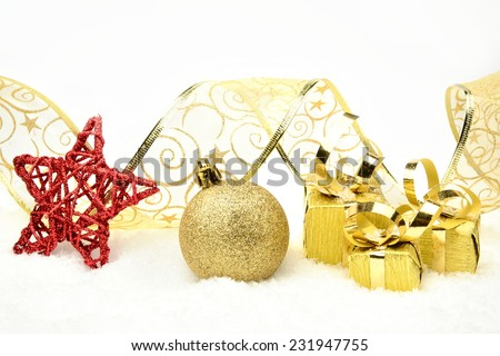 Decoration of golden christmas gifts,baubles,ribbon on snow withon white