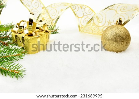 Decoration of golden christmas on snow with christmas tree branch - stock photo