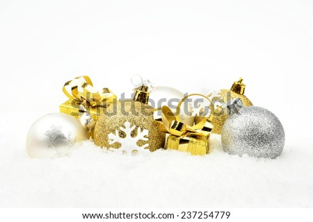 Decoration of golden,silver christmas baubles and gifts on snow white background - stock photo