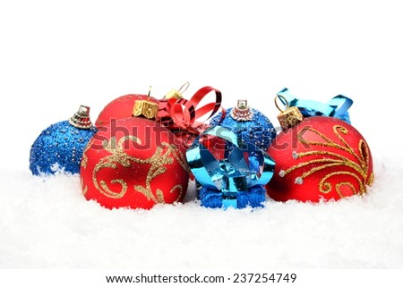 Decoration of red,blue christmas baubles and gifts in line on snow white background - stock photo