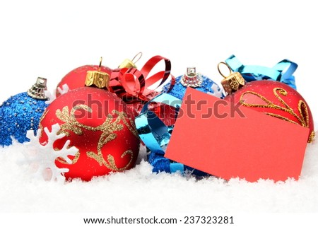 Decoration of red,blue christmas baubles and gifts in line on snow with wishes card on white background - stock photo