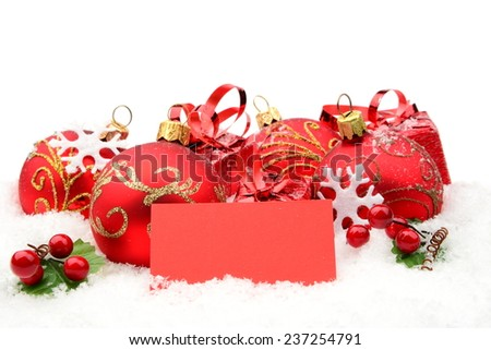 Decoration of red christmas baubles and gifts with wishes card on snow white background - stock photo