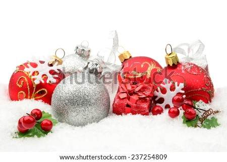 Decoration of red,silver christmas baubles and gifts on snow white background