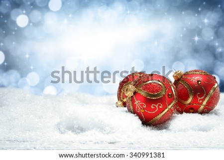 decoration of retro red ball on snow top and blue lights of wall of winter time  - stock photo