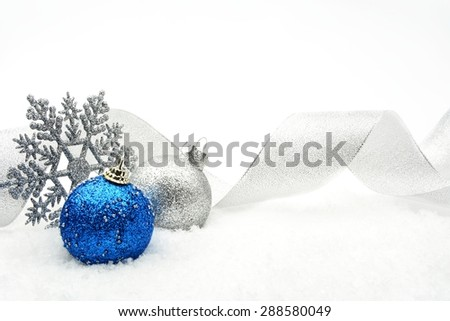 Decoration of silver and blue glitter baubles with ribbon and snowflake on snow on white background - stock photo