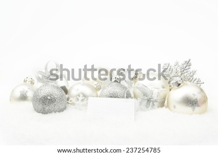Decoration of silver christmas baubles and gifts with wishes card on snow white background