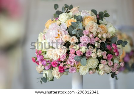 Decoration of wedding posy of fresh beautiful flowers of roses and peony white pink violet purple yellow lilac and orange colours in slim vase indoor, horizontal picture - stock photo