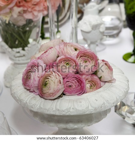 decoration of wedding table. pink ranunculus (persian buttercup) in vase on white table - stock photo