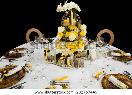 Decoration of wedding table with flowers, vases, and cages - stock photo