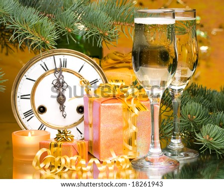 Decoration with an antique clock, firtree branch, gift boxes and champagne glasses