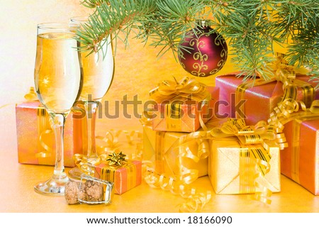 Decoration with an  firtree branch, gift boxes and champagne glasses