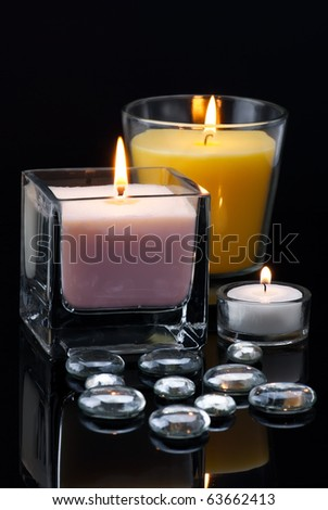 Decoration with burning candles and glass drops on black - stock photo