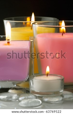 Decoration with colored burning candles and glass drops - stock photo