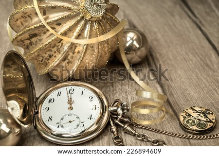 Decorations and vintage watch showing five to twelve. Happy New Year! - stock photo