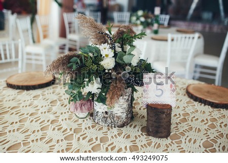 decorations of wood and flowers on the tables for guests