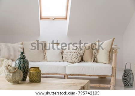 Decorative accessories on wooden table in front of beige sofa with pillows in room in the attic