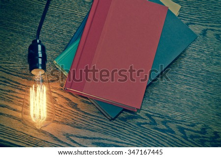 Decorative antique edison style filament light bulb and stack of books