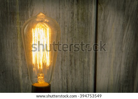 Decorative antique edison style filament light bulb with wooden fence background - stock photo