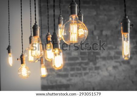Decorative antique edison style filament light bulbs against brick wall - stock photo