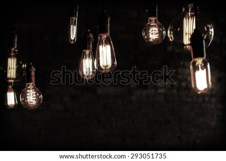 Decorative antique edison style filament light bulbs against brick wall - stock photo