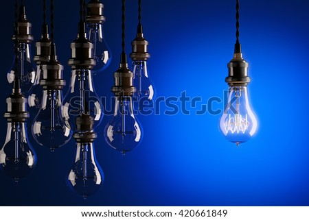 Decorative antique edison style light bulbs against a blue background. 3d render - stock photo