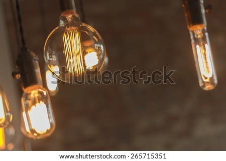 Decorative antique edison style light bulbs against brick wall background - stock photo