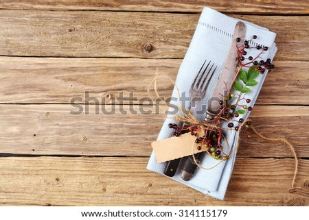 Decorative Autumn Table with cutlery and napkin on old rustic wooden plate with copyspace - stock photo
