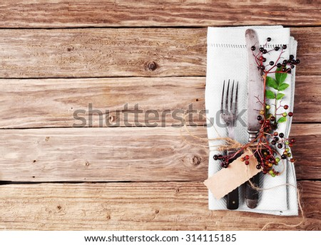 Decorative Autumn Table with flatware and napkin on old rustic wooden plate with copyspace - stock photo