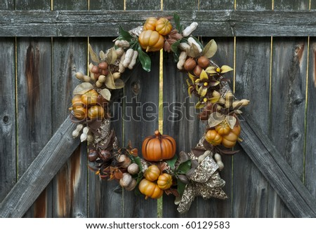 Decorative autumn wreath depicting various crops hanging on a rustic wooden fence. - stock photo