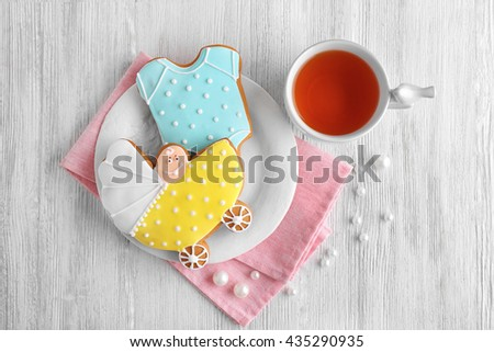 Decorative baby cookies with cup of tea - stock photo