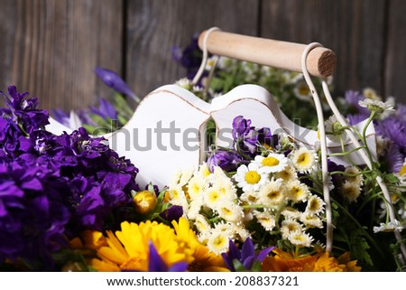 Decorative birds and beautiful wild flowers in basket on wooden background - stock photo