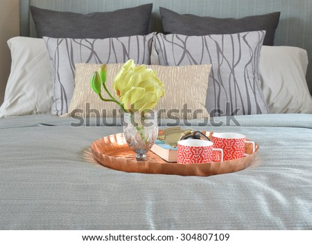 Decorative brass tray with glasses and sun glasses on bed