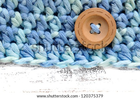 Decorative button on a crochet garment - stock photo