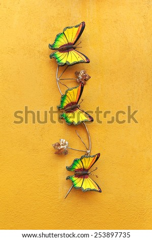 Decorative ceramic butterfly on yellow wall  - stock photo