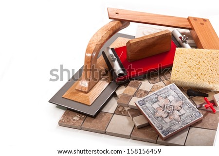Decorative ceramic tile, trowel, square, sponge, sand paper on a white background - stock photo
