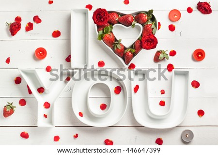 Decorative ceramics letters I Love You and Heart filled with strawberry and red roses on the white wooden background with candles for the romantic decor or St. Valentine's celebration - stock photo