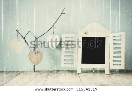 decorative chalkboard frame and wooden hanging hearts over wooden table. ready for text or mockup. retro filtered image with glitter overlay   - stock photo