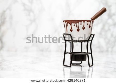 Decorative chocolate fondue bowl and stick on white marble background
