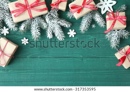 Decorative Christmas background with gifts tied with red ribbon amongst fresh pine branches with scattered snowflake ornaments on a green wooden table with copyspace for your greeting - stock photo