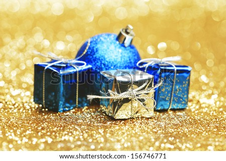 Decorative christmas ball and gifts close-up on golden background