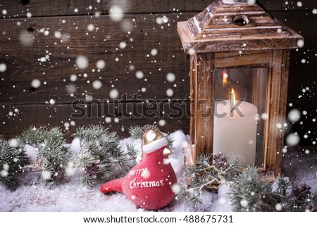 Decorative christmas composition. Burning candle  in lantern, christmas bird and branches fur tree on aged  wooden background.   Selective focus. Place for text. Drawn snow.