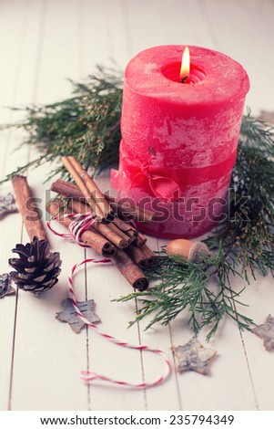 Decorative christmas composition - cinnamon,  candle, spruce, pine cone, stars on wooden background. Selective focus. - stock photo