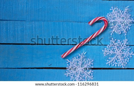 Decorative christmas composition - white snowflakes and candy cane on blue wooden  background - stock photo
