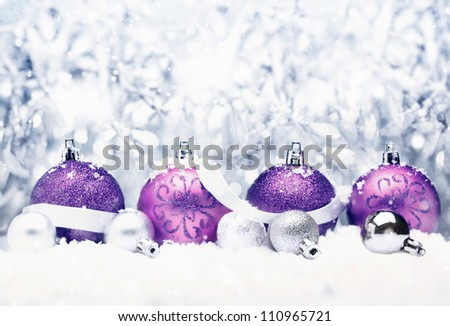 Decorative Christmas greeting with pretty purple baubles with festive silver bow and bokeh - stock photo