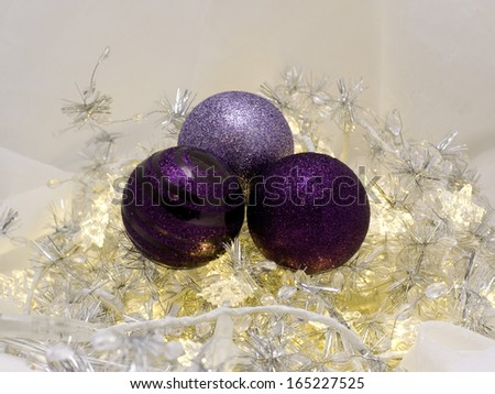 Decorative Christmas ornaments with pretty purple baubles and lights - stock photo