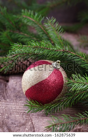 Decorative christmas postcard - spruce, ball on wooden background. - stock photo