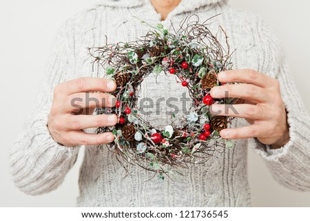 Decorative Christmas wreath held in hands of a man - stock photo