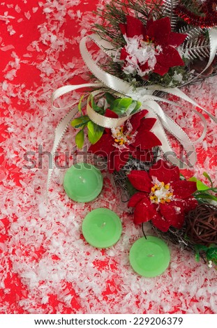 Decorative Christmas wreath on a red background with flowers poinsettia with snow. - stock photo