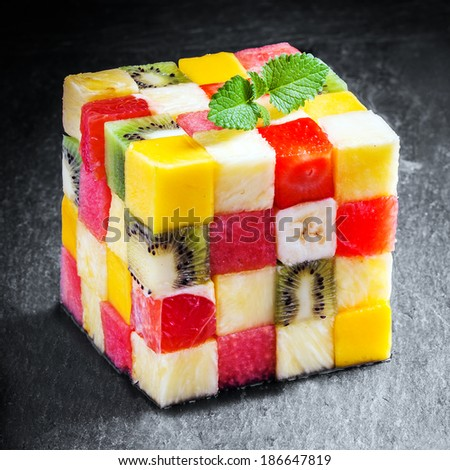 Decorative colorful cube of diced fresh summer tropical fruit composed of pineapple, watermelon, strawberry, banana, orange, strawberry and kiwifruit cut in squares for a geometric pattern - stock photo