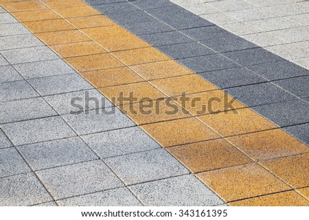 Decorative colorful sidewalk pavement. Tiled floor with grey tiles crossed by a diagonal double stripe of yellow and dark grey tiles viewed at a low angle, full frame background pattern - stock photo